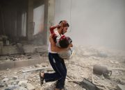 man-carries-injured-child-in-syria